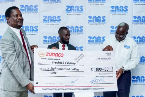 ZABS ED and Dean School of Education handing over the dummy cheque to Fredrick Chama